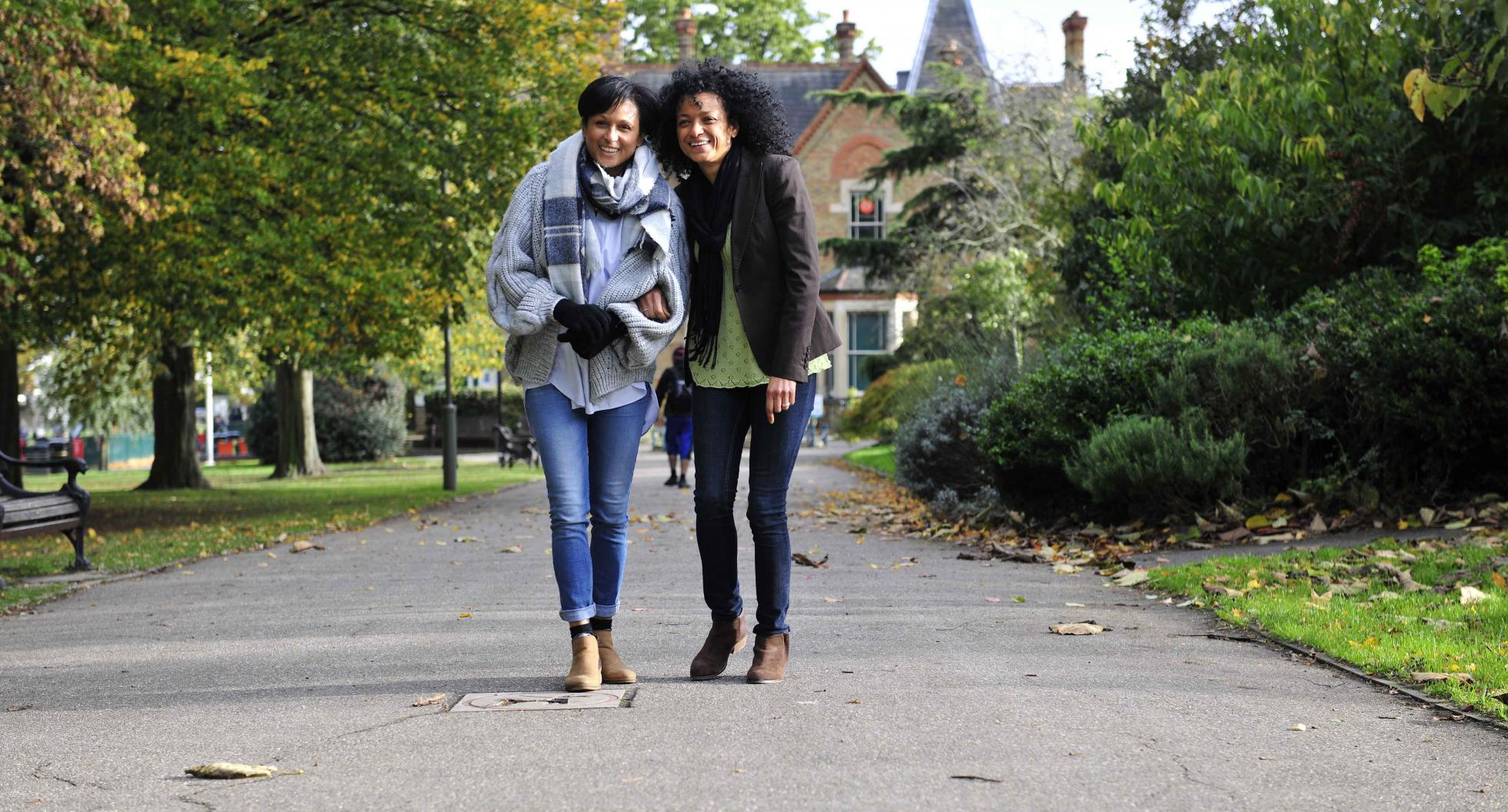 Two women walking through park