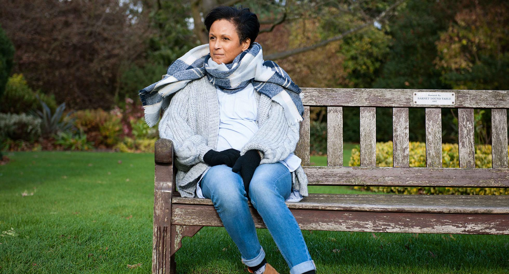 Woman sitting on park bench on a windy day