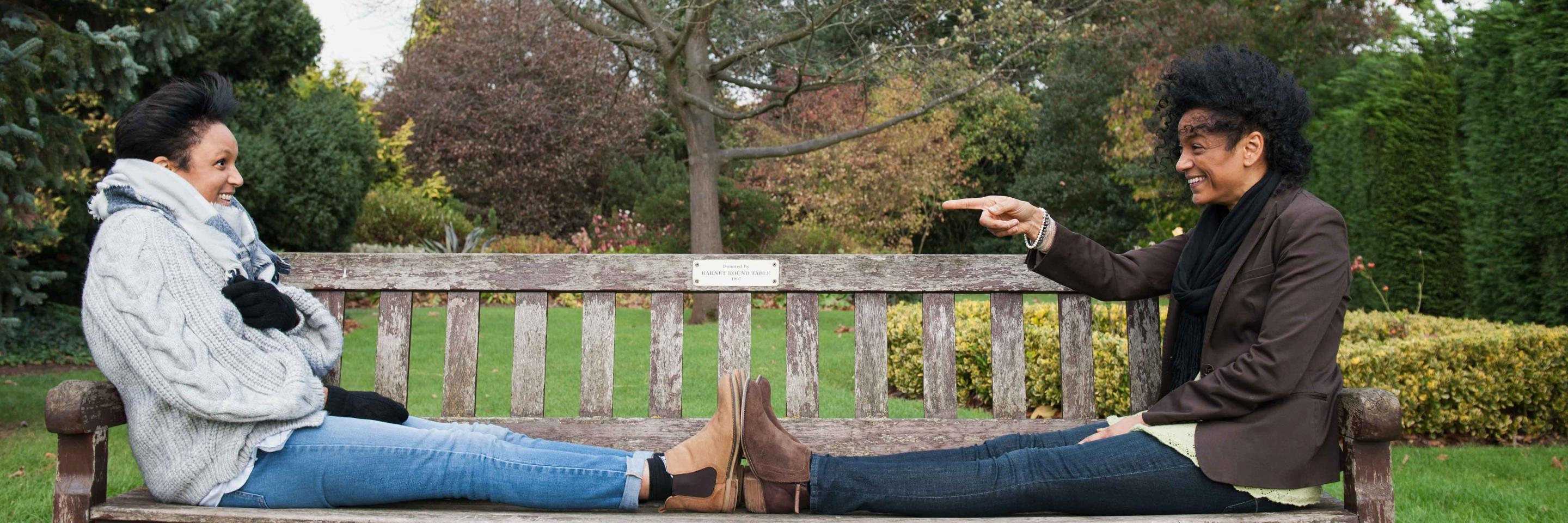 Woman pointing to another woman sitting on park bench