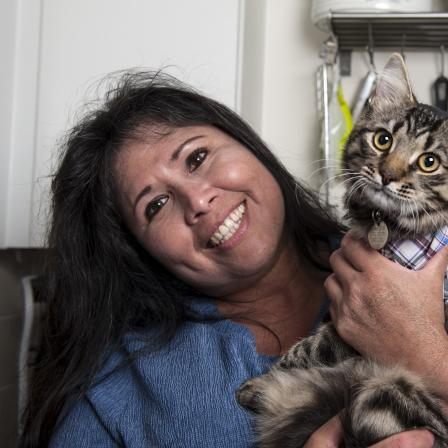 Woman smiling and holding her pet cat