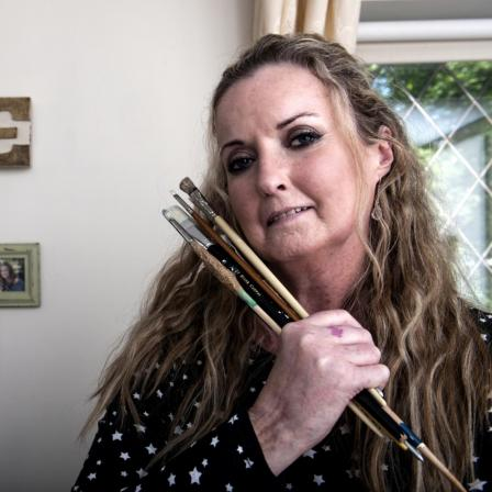 Woman with scleroderma with paintbrushes