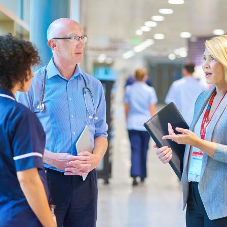 Consultants discussing with nurse in a hospital
