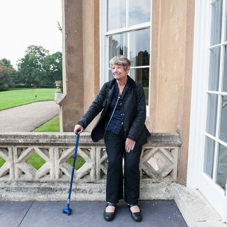 Woman with scleroderma standing outside with walking stick